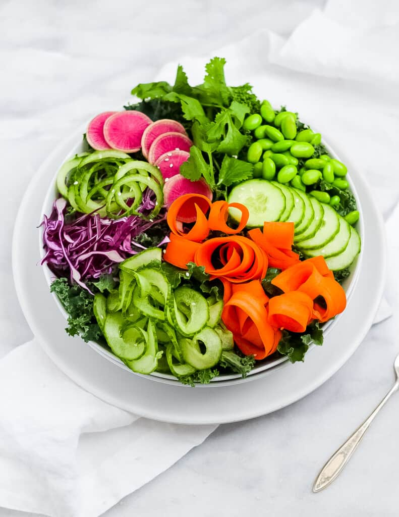 Picture of a sesame salad with a base of green kale, spiralized cucumbers, curly carrot ribbons, shredded red cabbage, shelled edamame, and thinly sliced cucumbers and pink watermelon radishes in a white bowl.