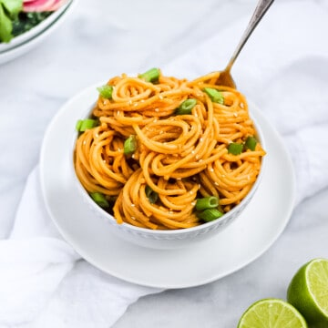 Picture of a white bowl of spaghetti noodles with peanut sauce and garnished with sliced green onions and white sesame seeds.