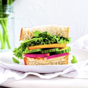 Fresh Vegetable Sandwich on a white plate with two slices of sourdough bread, green leaf lettuce, orange heirloom tomato, sliced cucumbers, radishes, and hummus.