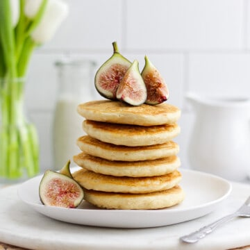 Stack of vegan pancakes on a white plate with sliced figs on top and white tulips in the background.