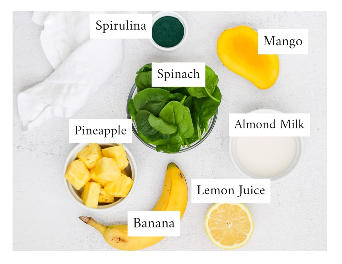 Picture of labeled ingredients; spirulina powder, mango, spinach, almond milk, pineapple, banana, and a lemon, on a white concrete surface with a white dish towel.