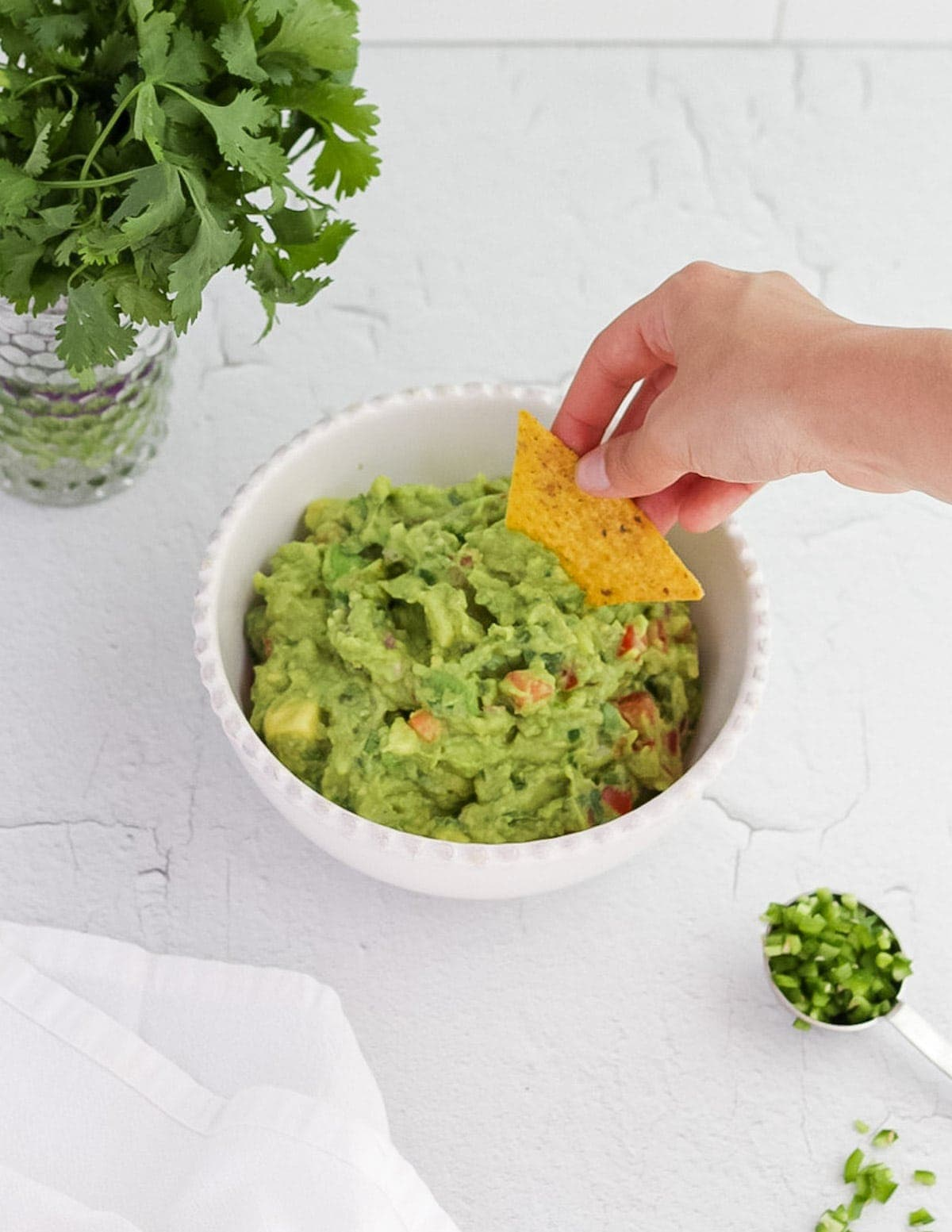 A hand reaching down and dipping a tortilla chip into a bowl of guacamole.