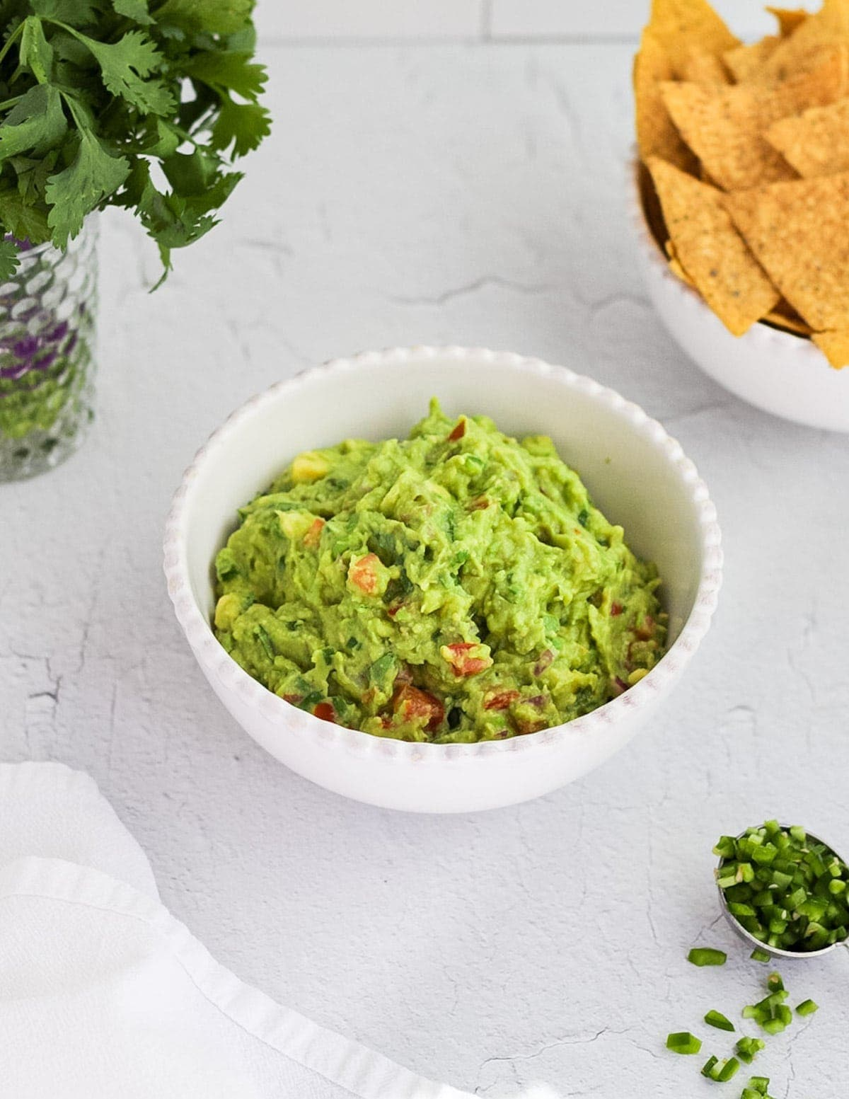 A picture of guacamole in a white bowl surrounded by ingredients.