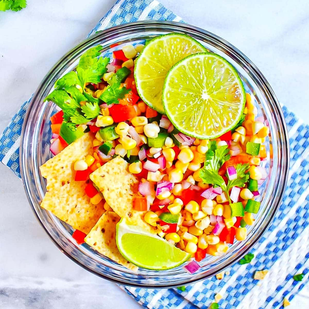 Picture of corn salsa in a round, glass bowl, garnished with sliced limes, cilantro, and tortilla chips.