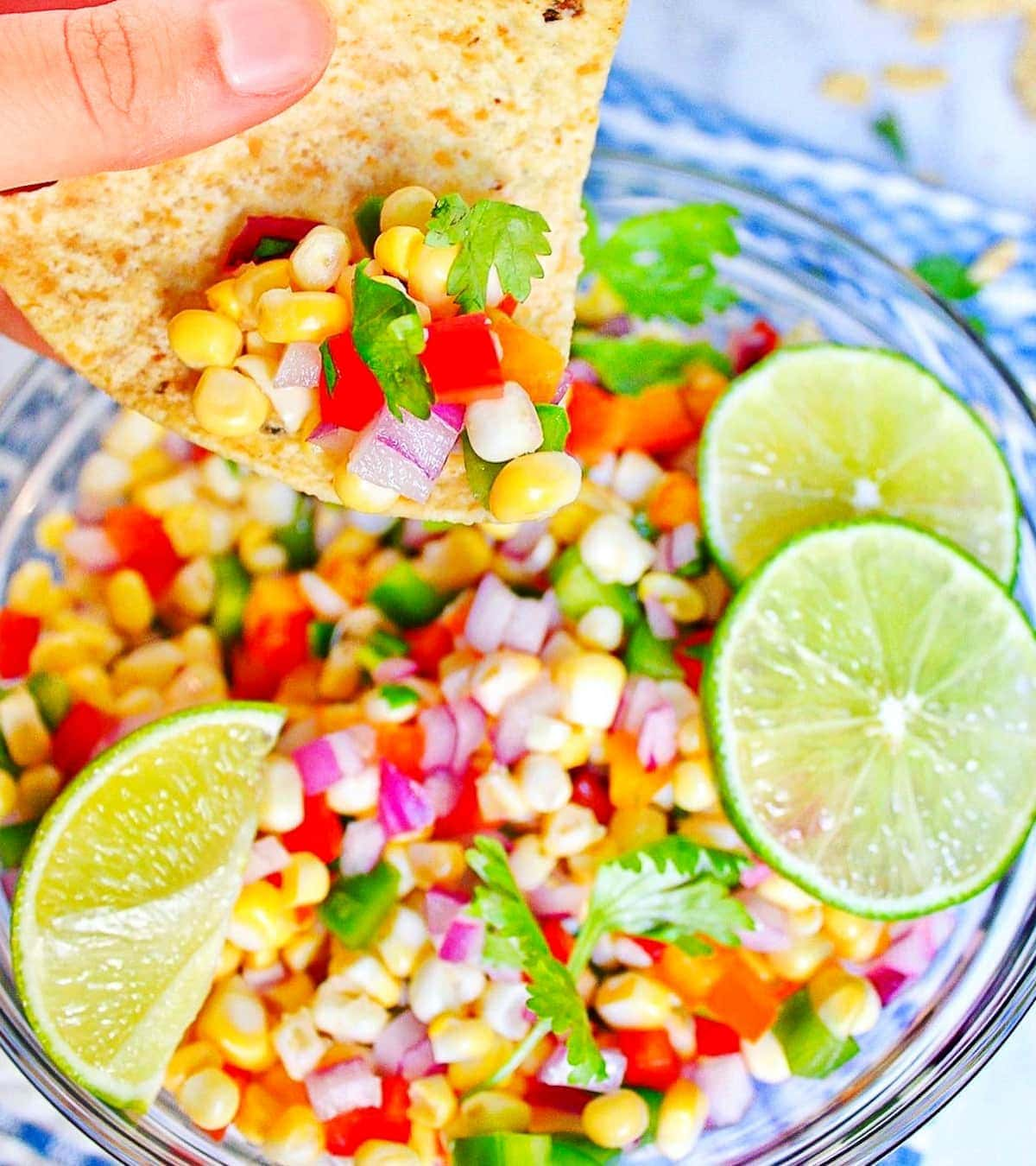 A hand holding a tortilla chip that is scooping corn salsa out of a round bowl.