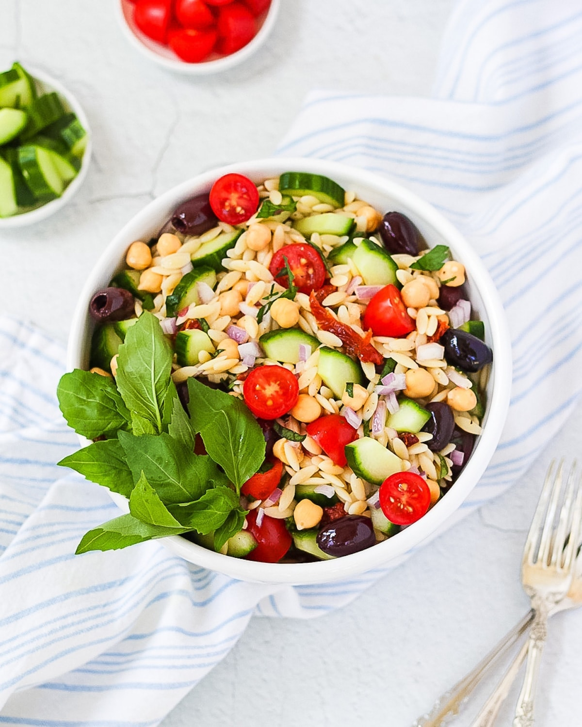 Picture of orzo salad in a white bowl garnished with a handful of fresh green basil leaves.