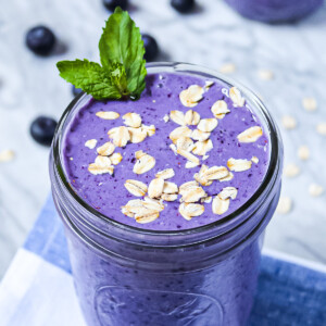 A purple/blue smoothie in a mason jar, garnished with uncooked oatmeal and a bright green sprig of mint. There are blueberries and oats in the background.