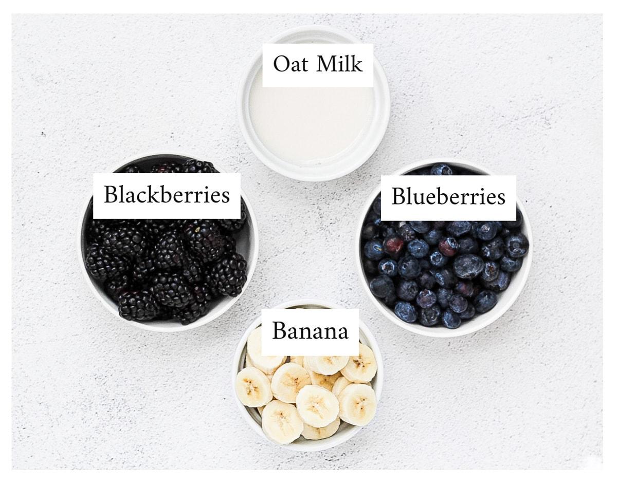White bowls, each holding: oat milk, blackberries, blueberries, and sliced banana.