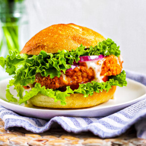A buffalo cauliflower sandwich on a white plate. The sandwich includes lettuce, buffalo cauliflower, tomato, red onion, and ranch dressing on a bun.