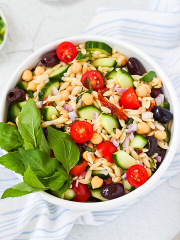 A white bowl sitting on top of a blue and white dish cloth. Inside the bowl is a Mediterranean Orzo Salad with orzo, chickpeas, tomato, olives, sun-dried tomatoes, red onion, and fresh herbs.