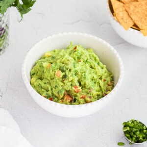A small white bowl holding guacamole. There are diced peppers, chips, and cilantro in the background.
