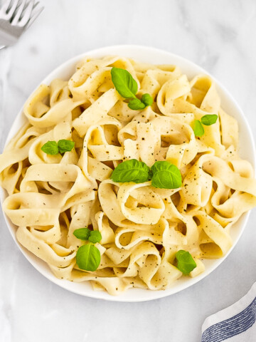 A white bowl holding bright yellow lemon pasta. Garnished with fresh basil. There are forks and a blue and white striped dish cloth in the background.