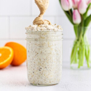 A picture of a clear mason jar with overnight oatmeal inside. A spoon is drizzling peanut butter on top. There are pink tulips and a sliced orange in the background.