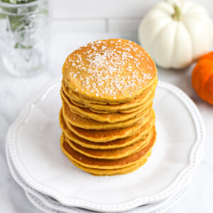 A stack of orange pumpkin pancakes on a stack of white plates. There are pumpkins in the background.