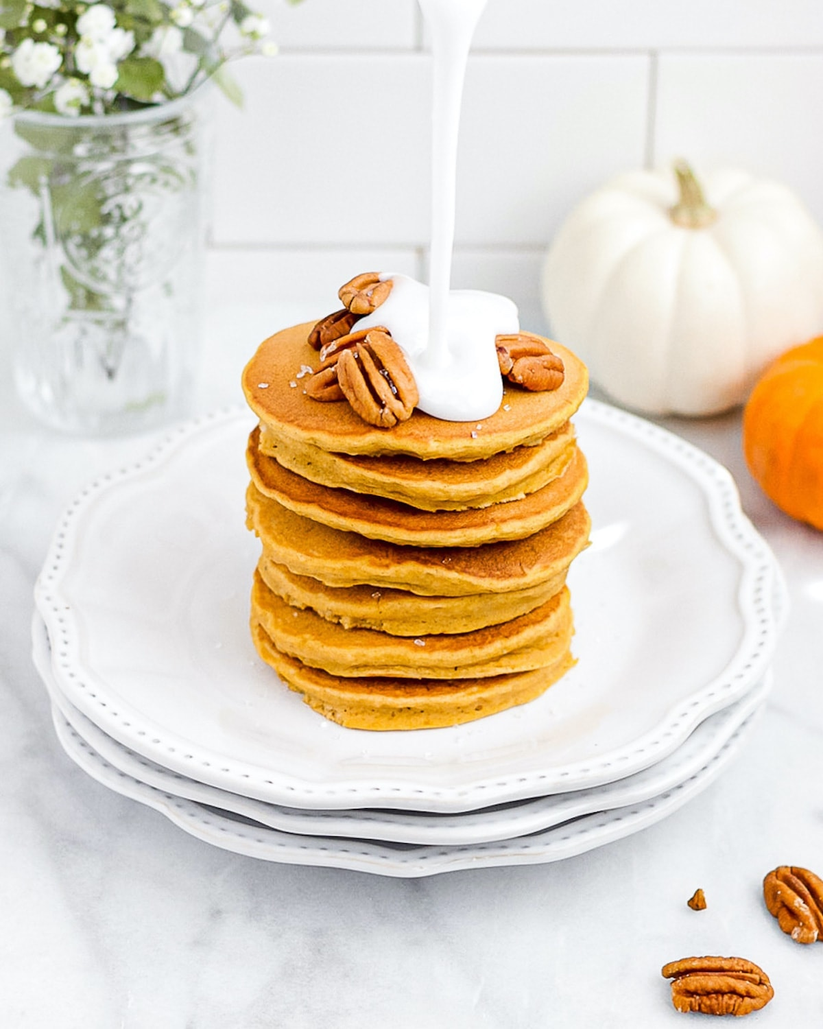 A stack of 7 pancakes sitting on three white plates, garnished with sugar, pecans, and a drizzle of white sugar glaze. The background has pecans, pumpkins, and green and white flowers.