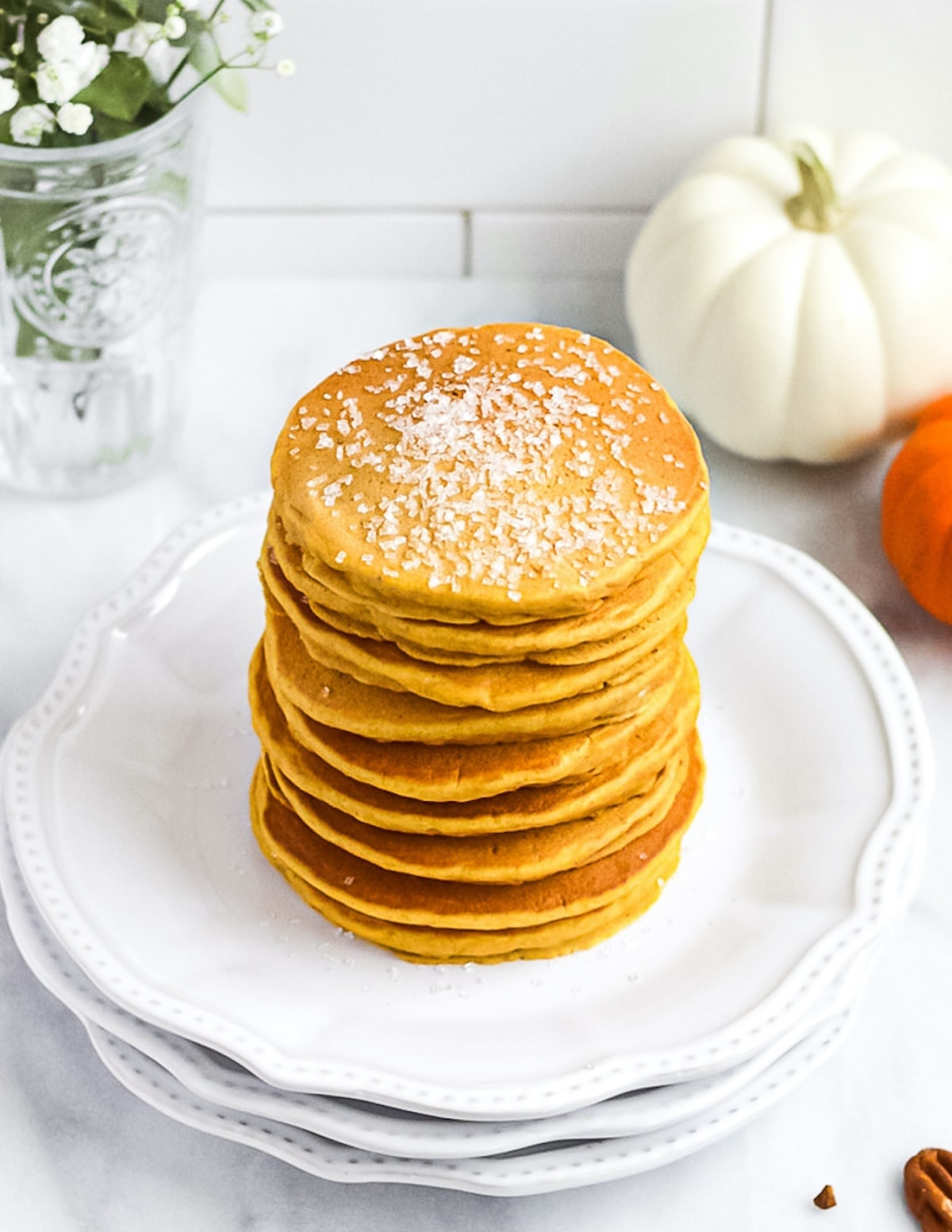 A stack of orange pumpkin spice pancakes with sugar sprinkled on top. There are pumpkins, flowers, and pecans in the background of the picture.