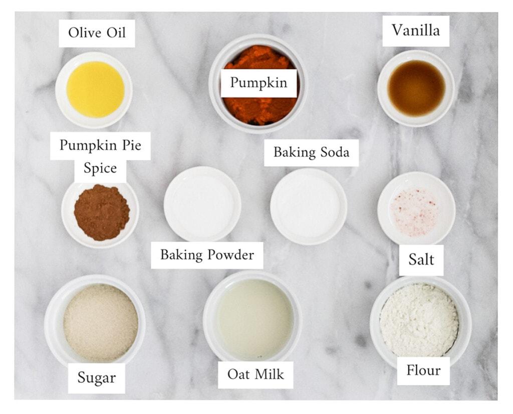 Small white bowls containing the ingredients for pumpkin pancakes, including: olive oil, pumpkin puree, vanilla, pumpkin pie spice, baking powder, baking soda, salt, sugar, oat milk, and flour.