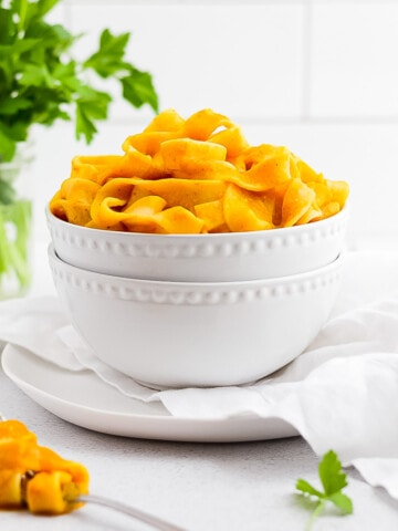 Two white stacked bowls holding pumpkin pasta.