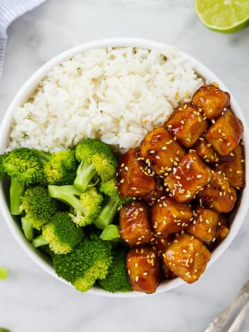 A white bowl holding sesame tofu, white rice, and broccoli.