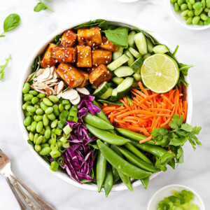 A white bowl holding a large salad, consisting of: sesame tofu, cucumbers, a lime, carrots, snap peas, red cabbage, edamame, and almonds.