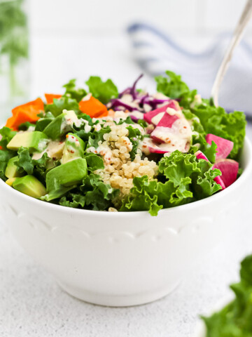 A white bowl holding a power bowl consisting of kale, quinoa, avocado, sweet potato, radishes, cabbage, and a tahini dressing on top.