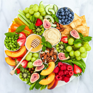 A white marble board filled with fresh fruits, vegetables, hummus, nuts, agave nectar, and garnished with fresh mint leaves.