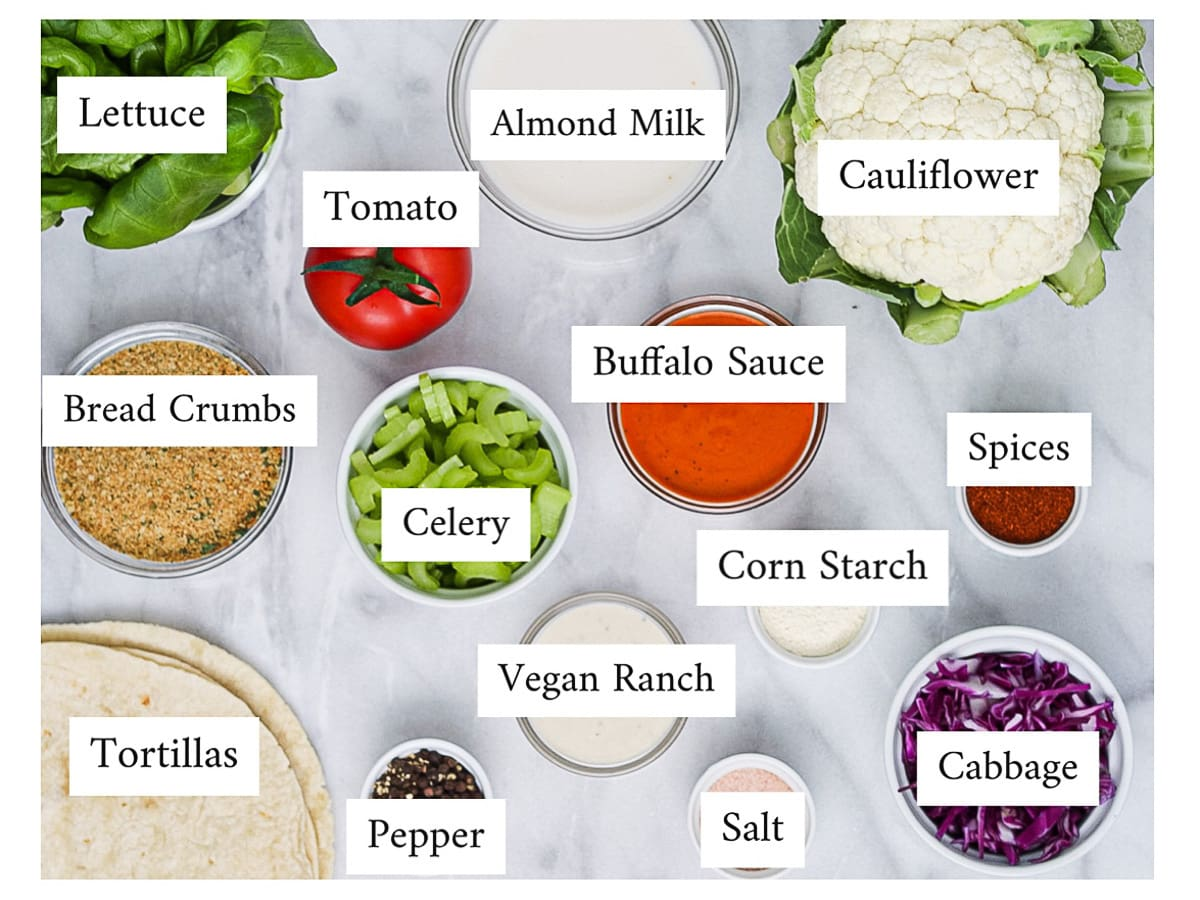 A picture of labeled ingredients: lettuce, bread crumbs, tortillas, tomatoes, celery, pepper, almond milk, buffalo sauce, vegan ranch, corn starch, salt, cauliflower, spices, and cabbage