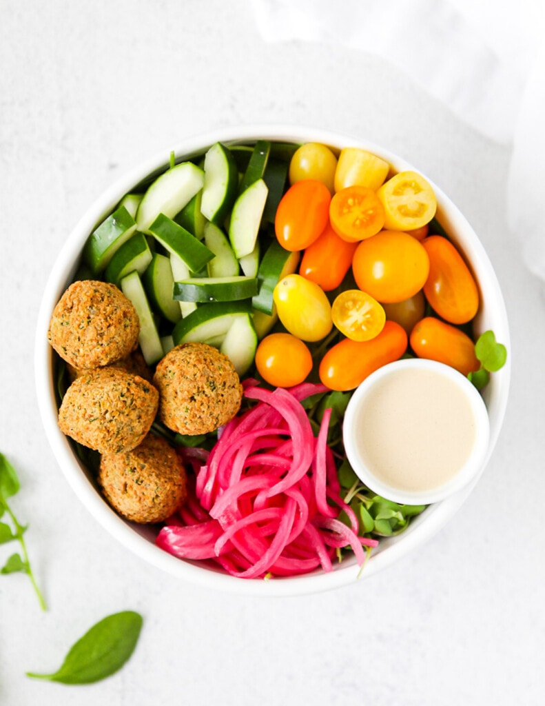 An overhead view of a white bowl with cucumber, tomato, tahini dressing, red onion, and falafel.