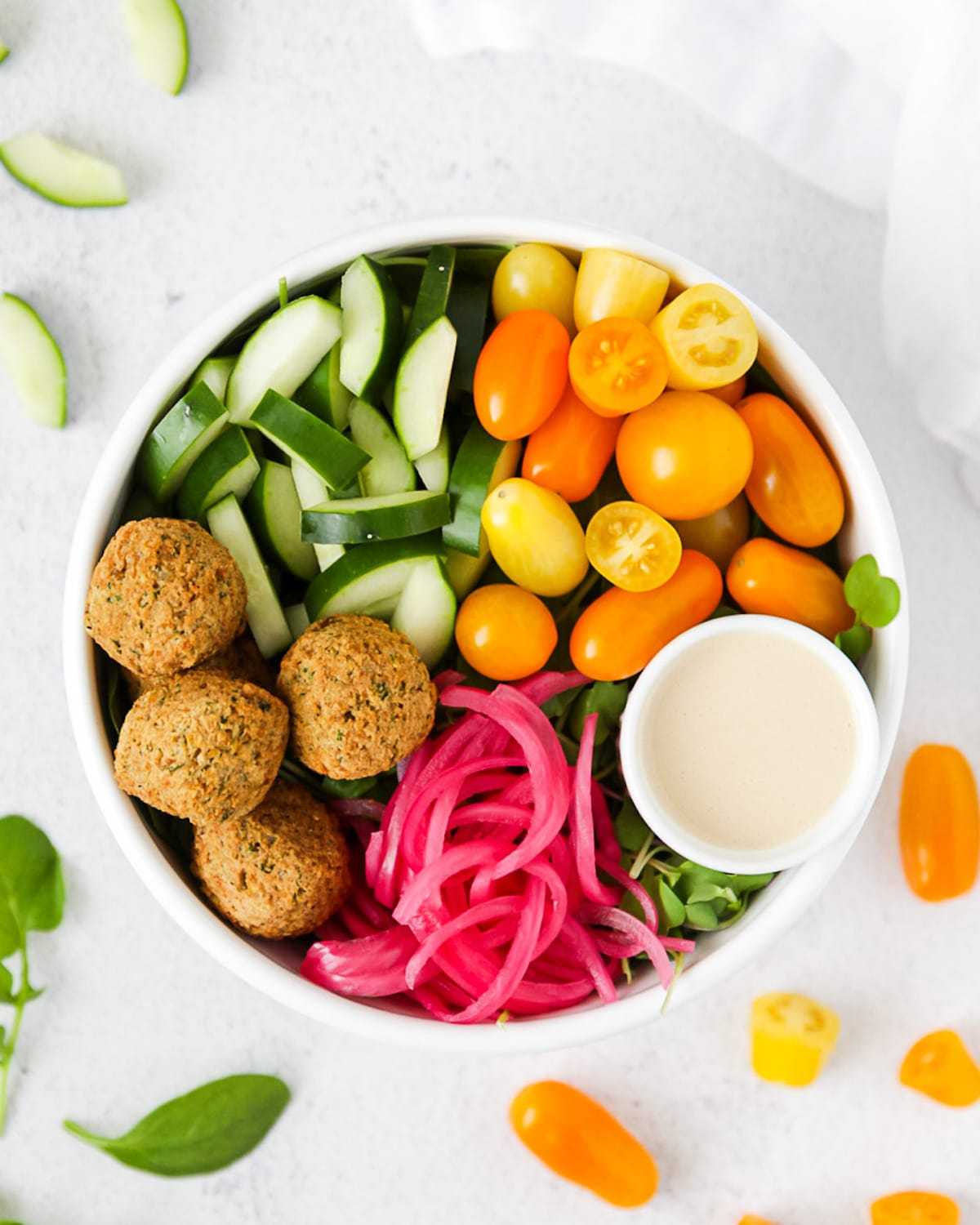A white bowl filled with: falafel, cucumber, tomatoes, tahini dressing, and pickled red onion. In the background there is a white linen cloth, sliced cucumber, spinach, and tomatoes.