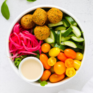 An overhead picture of falafel, cucumber, tomato, salad dressing, and pickled red onions in a white bowl