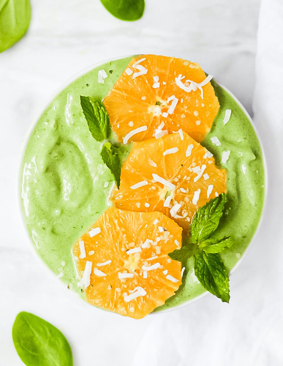 A large green creamy smoothie in a bowl. Garnished with peeled orange slices, mint, and white coconut flakes.