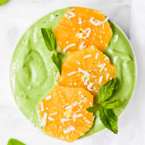 An overhead picture of a bright green spinach smoothie in a white bowl. It is decorated with oranges and green mint leaves, and a sprinkle of coconut flakes.