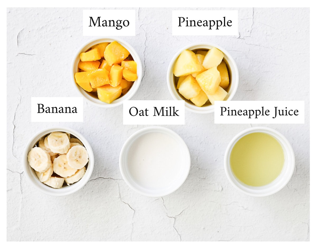 Small white bowls with labeled ingredients containing: mango, pineapple, banana, oat milk, pineapple juice