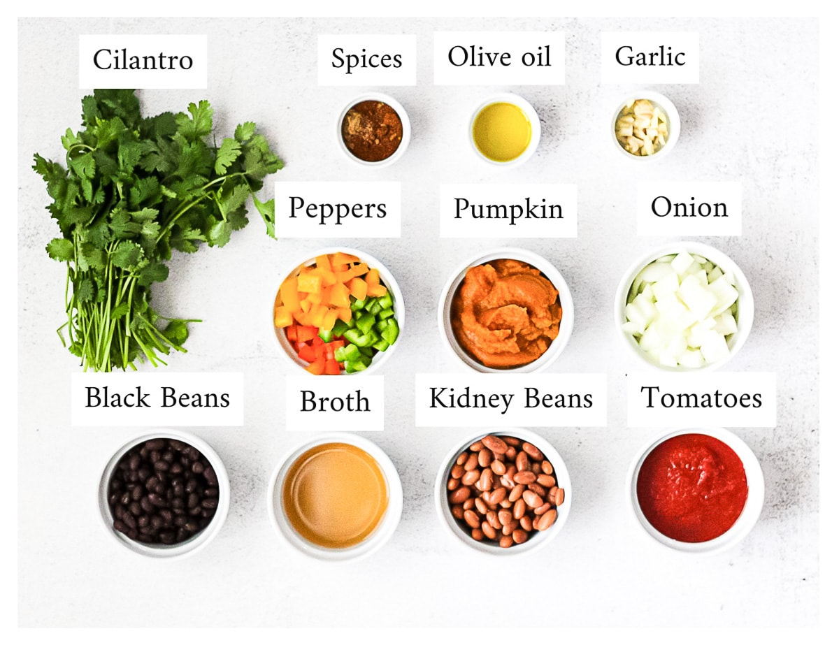 Ingredients for chili in small white bowls that are labeled with the ingredient name including: cilantro, spices, olive oil, garlic, peppers, pumpkin, onion, black beans, broth, kidney beans, tomatoes