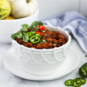 A white patterned bowl with chili inside, garnished with jalapeño peppers, habanero peppers, and cilantro. There is a bowl of pumpkins, a blue and white cloth, and a sliced jalapeño in the background.