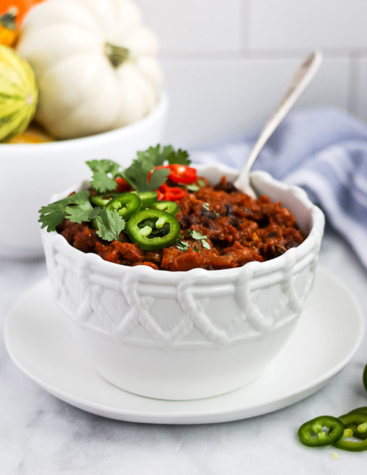 Chili in a bowl with a spoon dipped in, and peppers and cilantro on top. The background has a bowl of pumpkins, a blue cloth, and sliced peppers.