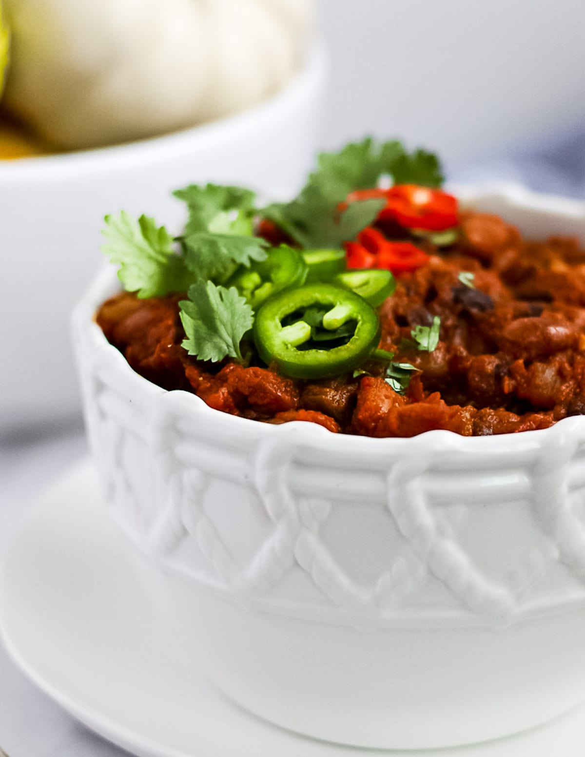 A close up shot of chili in a white patterned bowl. There are freshly sliced peppers and cilantro on top.