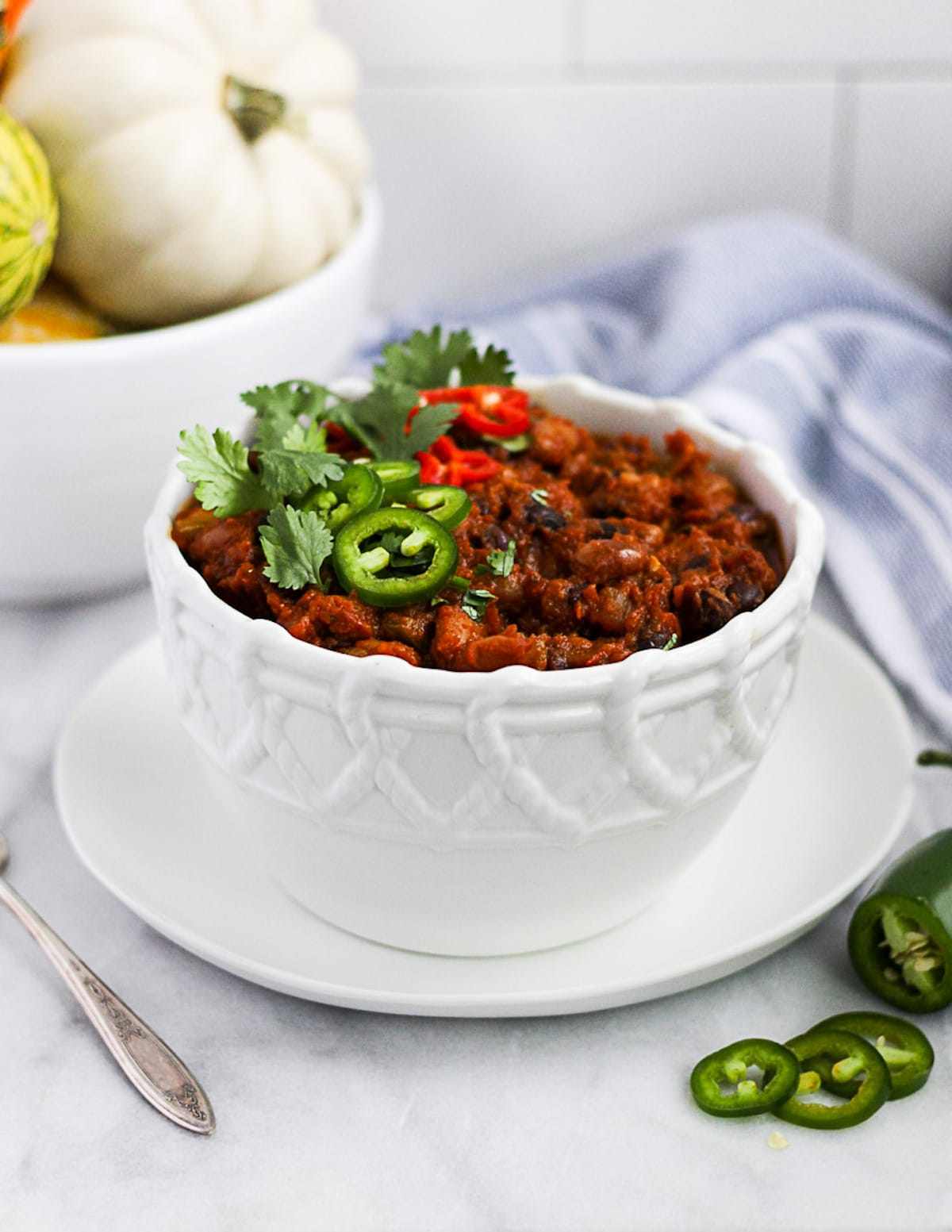 A large white bowl filled with vegan chili. There are peppers and cilantro on top. The background has a blue and white striped cloth, a white bowl filled with pumpkins, a sliced pepper, and a spoon.