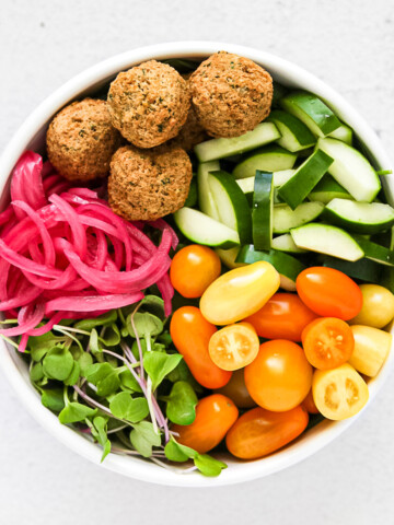 A large white bowl filled will cucumbers, tomatoes, greens, pink pickled red onions, and falafel.